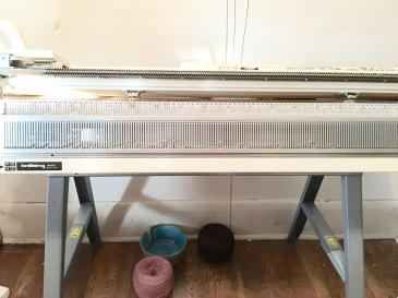 Knitting machine installed on sawhorse-based table