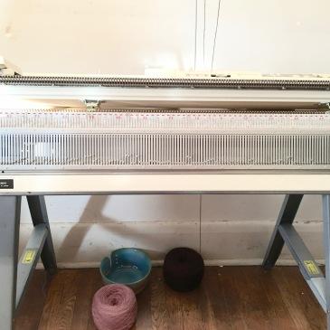 Knitting machine installed on sawhorse-based table