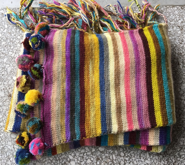 Striped machine-knit scarf with braided ends and pompoms