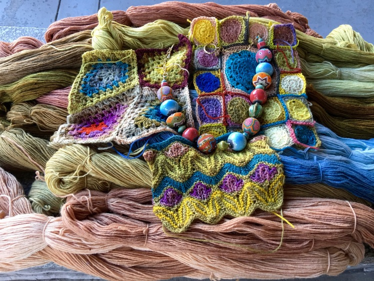Plant-dyed colors in skeins, crochet, knitting with complementary jewelry
