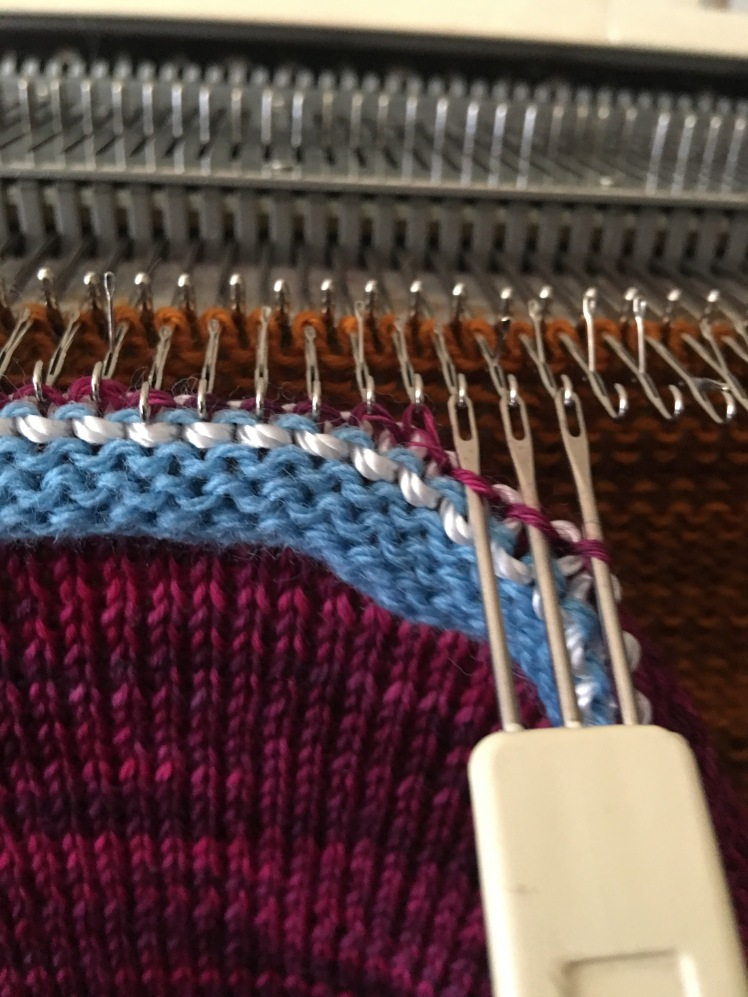 Close-up photo of transfer tool hanging stitches on knitting machine