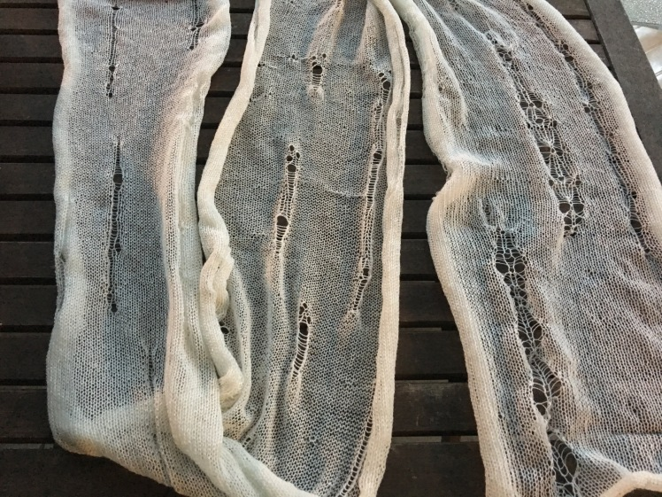 Machine-knit scarf with intentional holes and ladders, before dyeing and felting