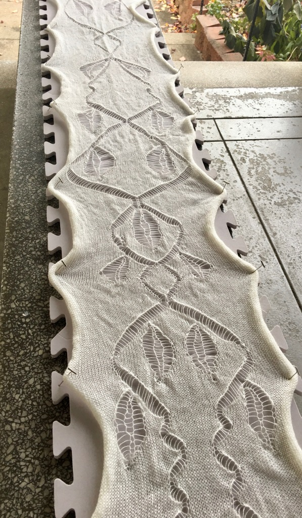Hand-manipulated lace stitches in machine-knit fabric