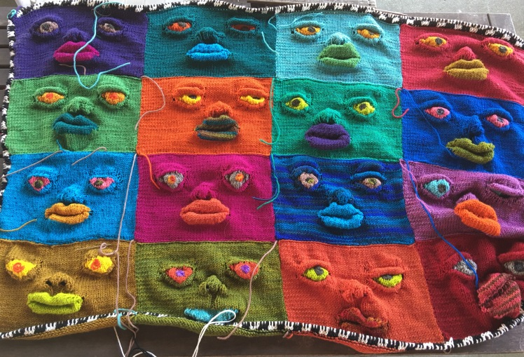 Wall hanging of knitted sculptural faces