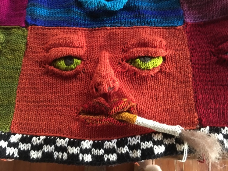 Knitted face with knitted cigarette