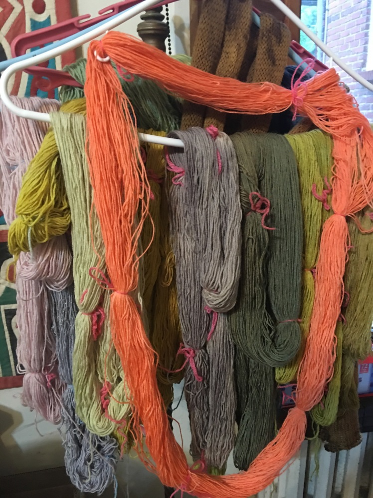 Plant-dyed yarn in subtle colors, offset by orange yarn