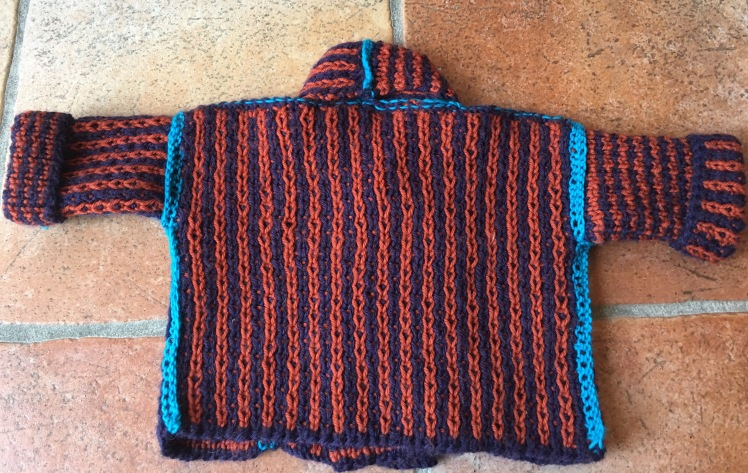 Knitted baby jacket with two-sided stitch pattern