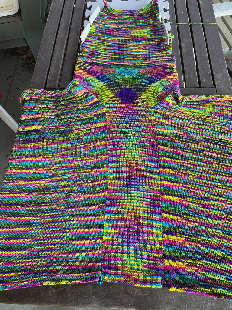 In-progress photo of panel joining front and back showing argyled pooling of black and neon multi yarn