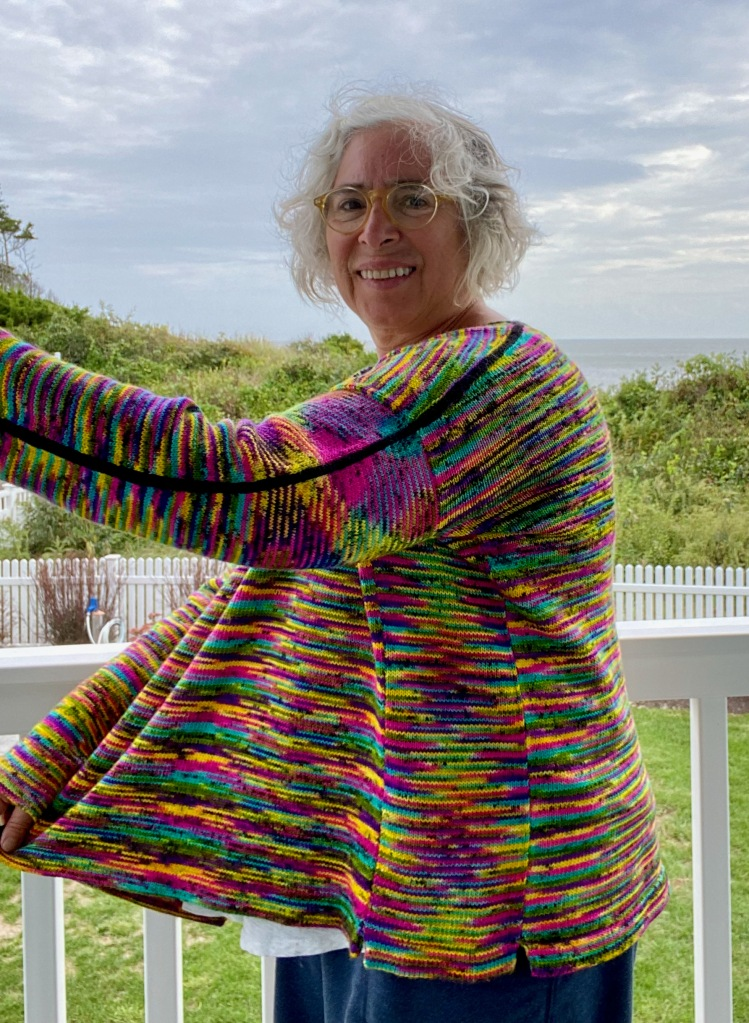 Modeled side view of black and neon pullover with front held out in front of body to show the construction of the garment