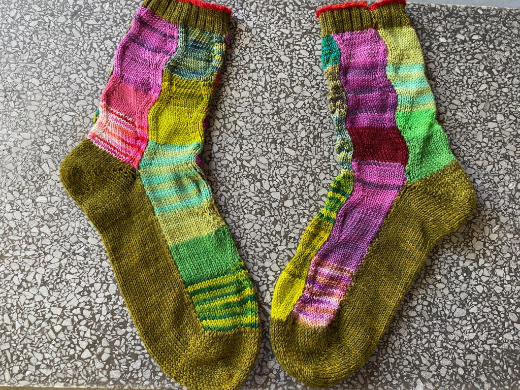 Two socks machine-knitted in wavy panels shaped with increases and decreases, using many different yarns in pinks and greens