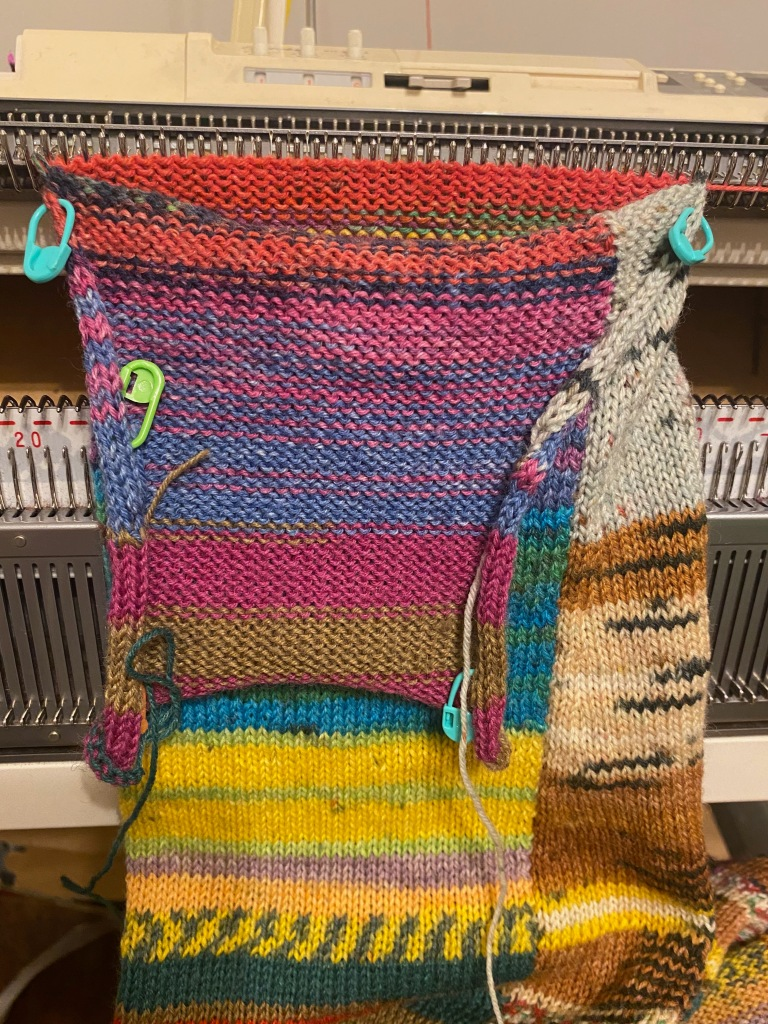 The sleeve is on the machine while the third and final panel is being knitted. This panel joins the sleeve into a tube